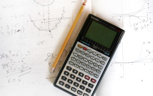 Pencil and calculator on paper with math notes