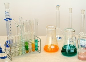 Various beakers and test tubes with colored liquids on a bench